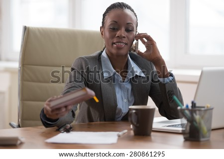 Business woman calling phone and writing something in her schedule book and papers at office workplace