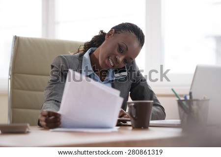 Business woman calling phone and writing something in her schedule book and papers at office workplace - stock photo