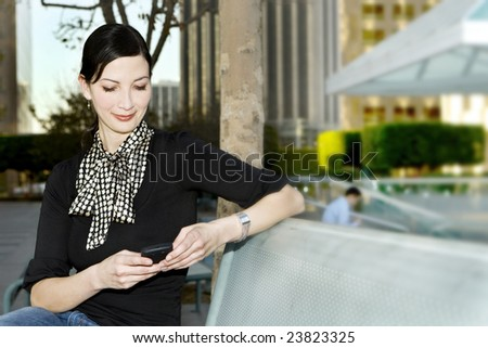 Business woman checking email on her phone - stock photo