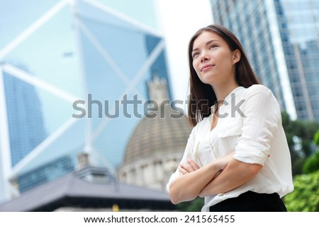 Business woman confident portrait in Hong Kong. Businesswoman standing proud and successful in suit cross-armed. Young multiracial Chinese Asian / Caucasian female professional in central Hong Kong. - stock photo