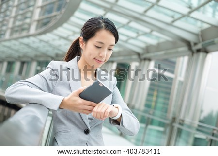 Business woman connecting smart watch and cellphone