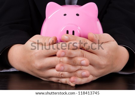 Business woman covering pink piggy bank. - stock photo