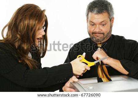 Business woman cutting man's tie stuck in paper shredder. - stock photo