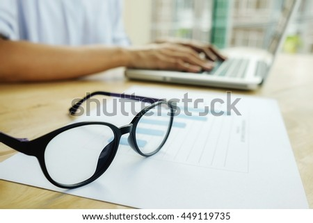 Business woman discussing data with new modern computer and charts. Glasses on analysis charts with business woman working with her computer background. Business concept.