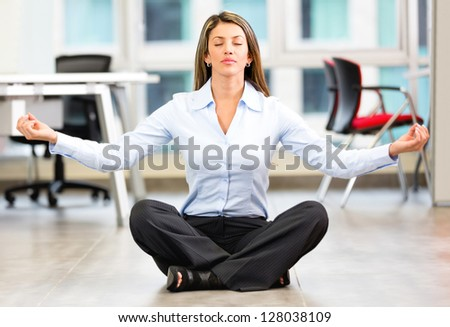 Business woman doing yoga at the office - stock photo