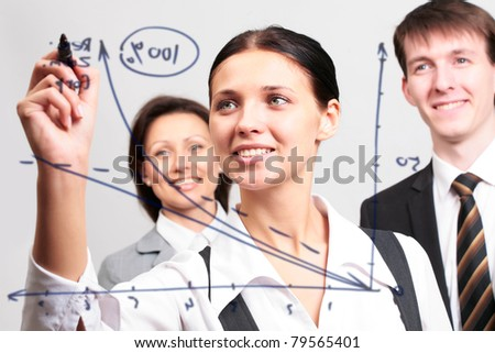 Business woman drawing a graph on a glass window in an office - stock photo