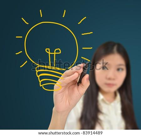 Business woman drawing light bulb of idea - stock photo
