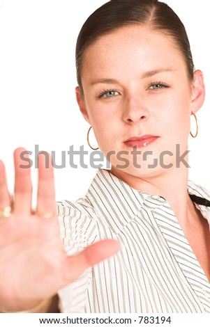 Business woman dressed in a white pinstripe shirt. Holding up hand. Shallow DOF, hand out of focus, face in focus - stock photo