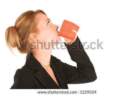 Business woman dressed in jeans and a beige jacket.  Drinking out of a mug - copy space