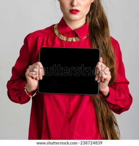 Business woman dressed in red holding and shows touch screen tablet pc with blank screen. - stock photo