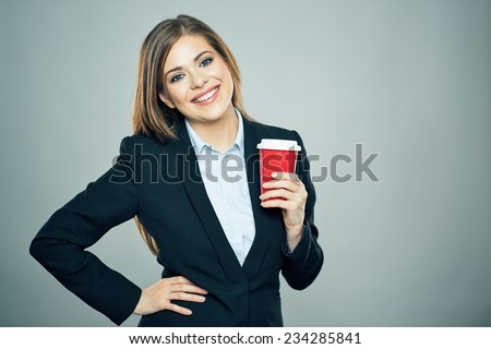 Business woman dressed office style suit smiling and hold red cup of hot drink. Isolated business portrait. - stock photo