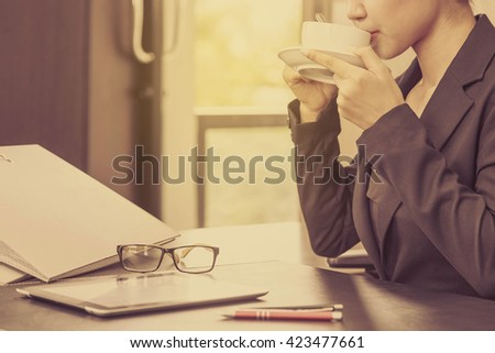 Business woman drinking coffee in the office. vintage - stock photo