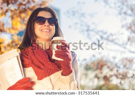 Business woman eating breakfast in autumn park - stock photo