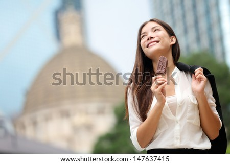 Business woman eating ice cream in Hong Kong. Young businesswoman enjoying ice-cream on at stick walking outside smiling happy in central Hong Kong. Mixed race Chinese Asian / Caucasian model on break - stock photo