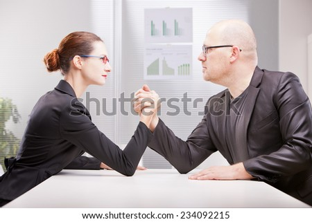 business woman facing business man and starting to perform an arm wrestling to decree who's best - stock photo
