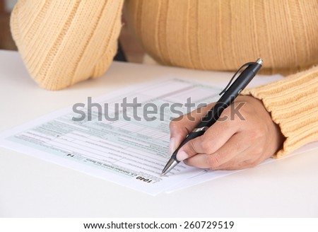 Business woman filing IRS tax form 1040 - stock photo