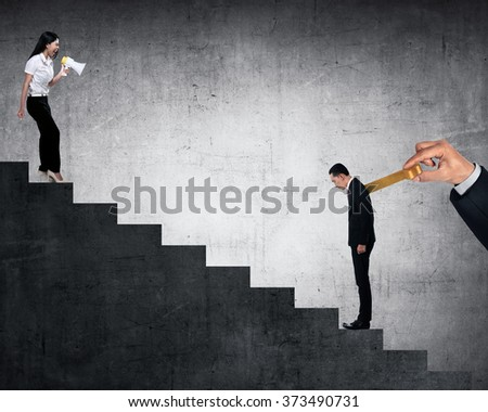 Business woman give order to her friend with winding key on his back - stock photo