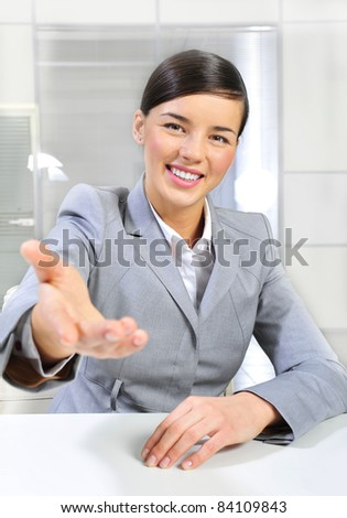 Business woman gives a handshake at her office. Vertical shot. - stock photo