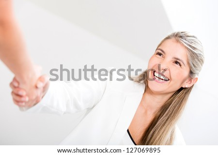 Business woman giving a handshake and looking happy - stock photo