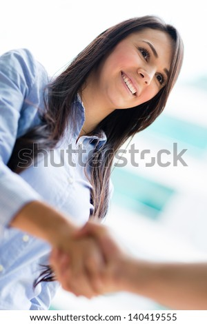 Business woman giving a handshake and smiling - stock photo