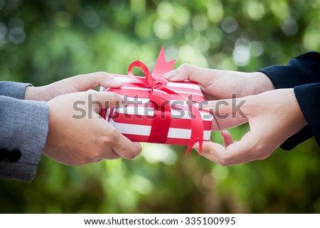 Business woman hand with christmas gift box on green bokeh background - stock photo
