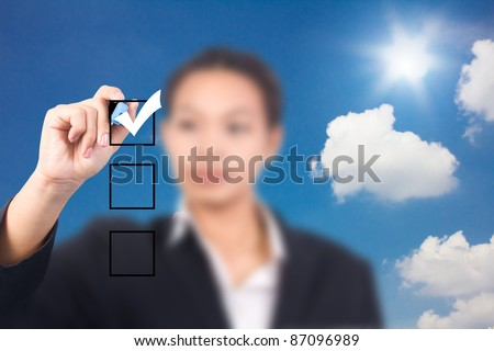 business woman hand with pen mark the check boxes. - stock photo