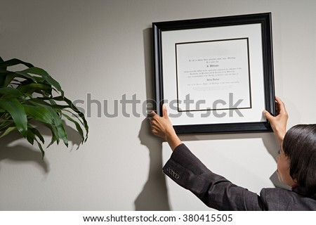 Business woman hanging framed certificate - stock photo