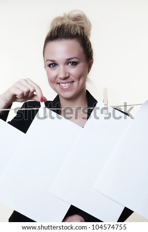business woman hanging out blank piece of paper on a washing line using wooden pegs - stock photo
