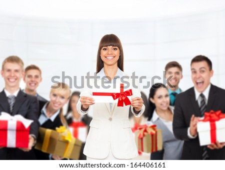 Business woman happy smile hold gift card present with red bow. Businesswoman over big group of people human resources background