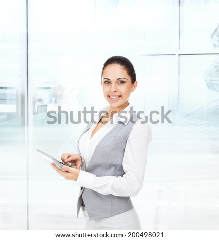business woman happy smile hold tablet pad computer empty touch screen with copy space, young businesswoman wear vest smiling in modern office - stock photo