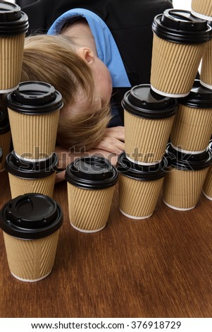 business woman has fallen asleep on the desk behind lots of takeaway drink cups. - stock photo