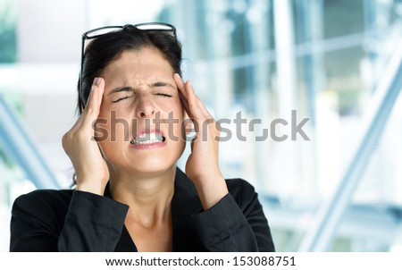 Business woman headache or anxiety attack crisis. Businesswoman suffering painful migraine or stress in work. - stock photo