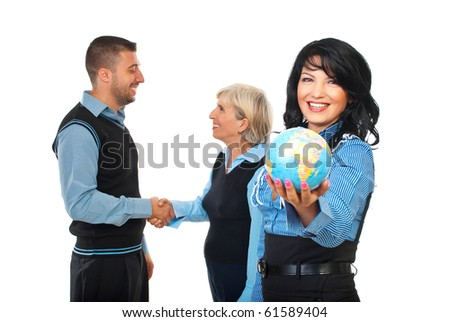 Business woman hold a world globe while two other business people shaking hands in background concept of international business relationship isolated on white background,selective focus on young woman - stock photo
