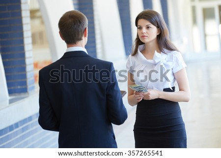 business woman hold money and a businessman hold a tablet