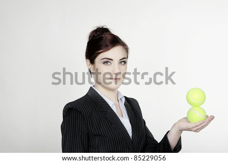 business woman hold out her arm with two tennis balls in her hand - stock photo