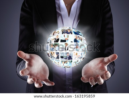 Business woman holding a ball of people on a dark background - stock photo
