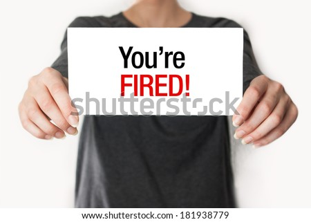 Business woman holding a card with you're fired text - stock photo
