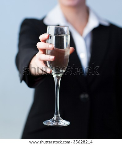 Business woman Holding a Champagne Glass with the camera focus on the glass - stock photo