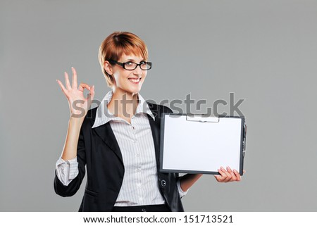 Business woman holding a clipboard and gesturing isolated on grey - stock photo