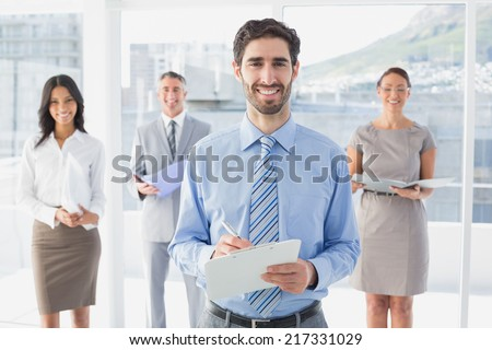 Business woman holding a clipboard with co-workers - stock photo