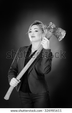 business woman holding a large axe shot in the studio on a gray background