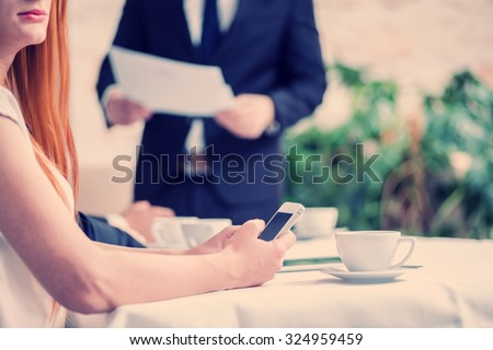 Business woman holding a mobile phone in their hands while confident businessman sitting at the table at a business meeting in the office and keep the documents in his hand - stock photo