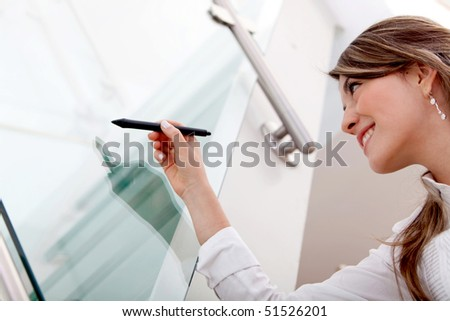 Business woman holding a pen to write a graph on a screen - stock photo
