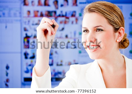 Business woman holding a pen to write on a screen - stock photo