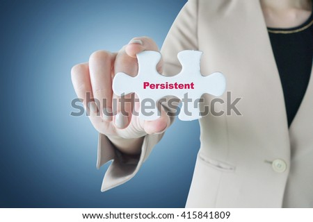 Business woman holding a piece of jigsaw puzzle with word Persistent as personality concept - stock photo