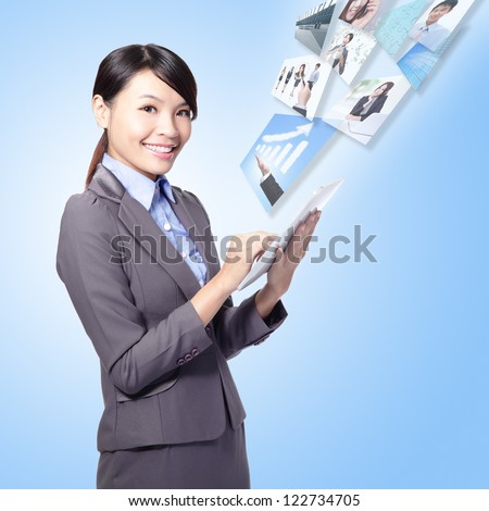 business woman holding a tablet pc and work with internet isolated on blue background, model is a asian girl - stock photo