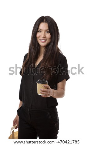 business woman holding a take away cup and carrying her lunch on her break from the office