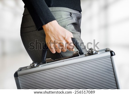 Business woman holding an aluminum briefcase and hurrying to work. Confident woman preparing for important negotiations and deals. Money and documents in safe hands of office worker. - stock photo