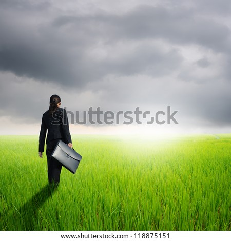 Business woman holding bag in green rice field and rainclouds