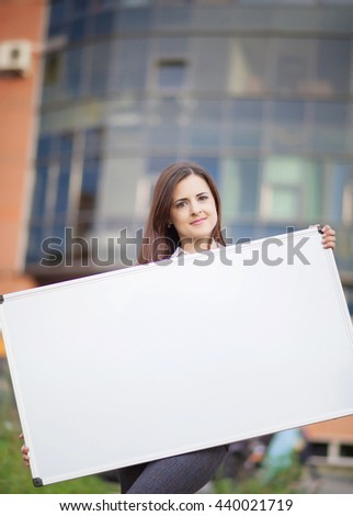Business woman holding banner ad in her office  - stock photo